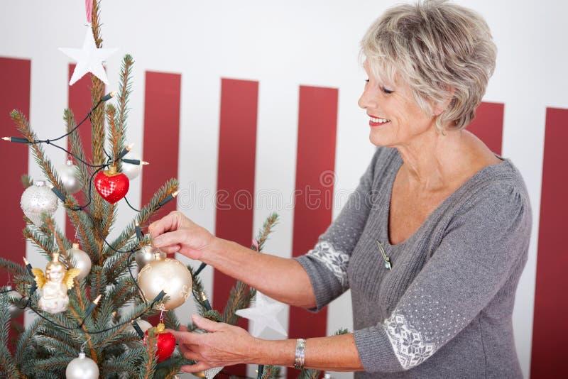 资深妇女垂悬的圣诞节装饰 免版税库存图片