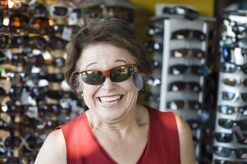 资深妇女尝试的太阳镜在商店 库存照片