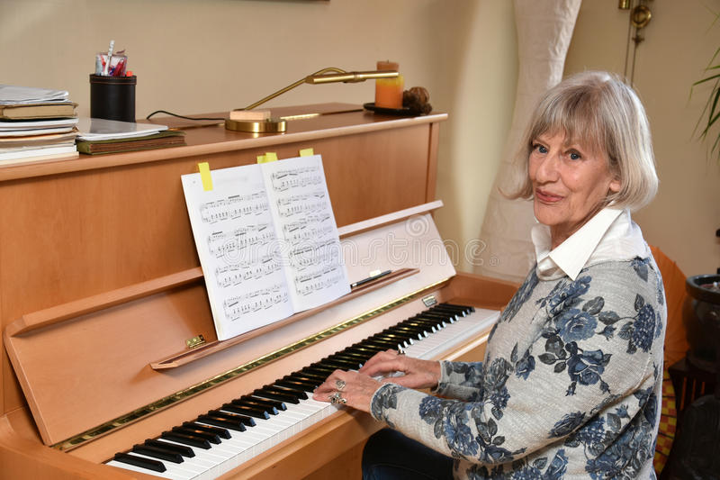 资深妇女弹钢琴 免版税库存照片