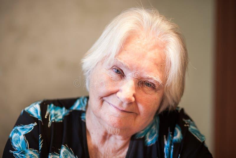 资深妇女微笑到照相机里,晚年祖母 免版税库存照片