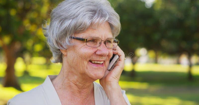 资深妇女微笑和谈话在电话 免版税库存照片