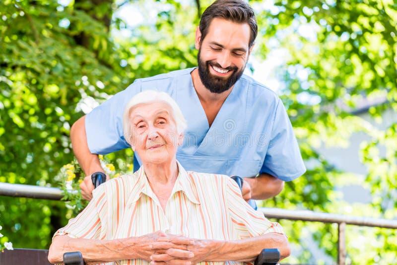 给资深妇女按摩的老年医学的护士 免版税库存照片