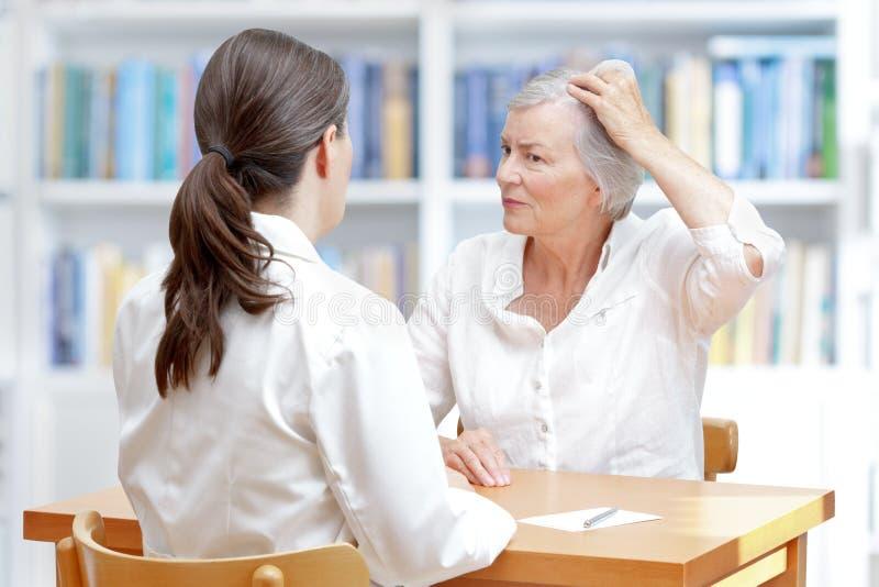 资深妇女掉头发医生 免版税库存图片