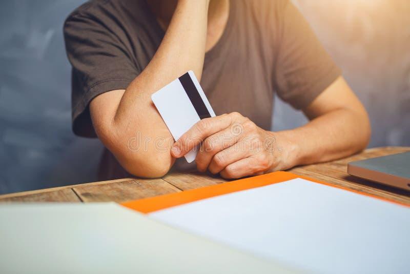 资深妇女显示她的在老木桌上的信用卡与灰色 免版税库存图片