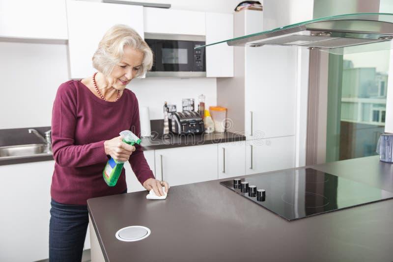 资深妇女清洁厨台 免版税库存图片