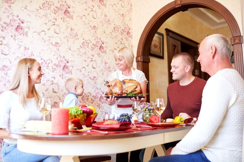 资深妇女用一个庆祝的家庭的烤火鸡在轻的背景 传统概念 复制空间 库存照片
