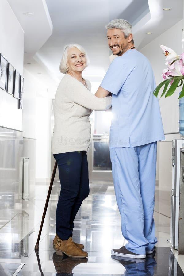 资深妇女用站立在修复铈的棍子和生理治疗师 免版税图库摄影