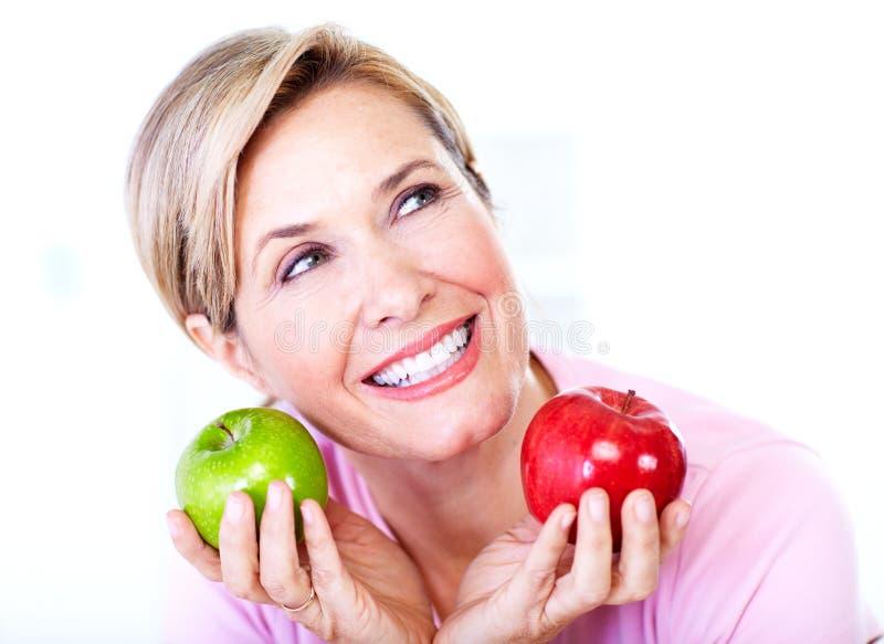 资深妇女用苹果。饮食。 免版税库存图片