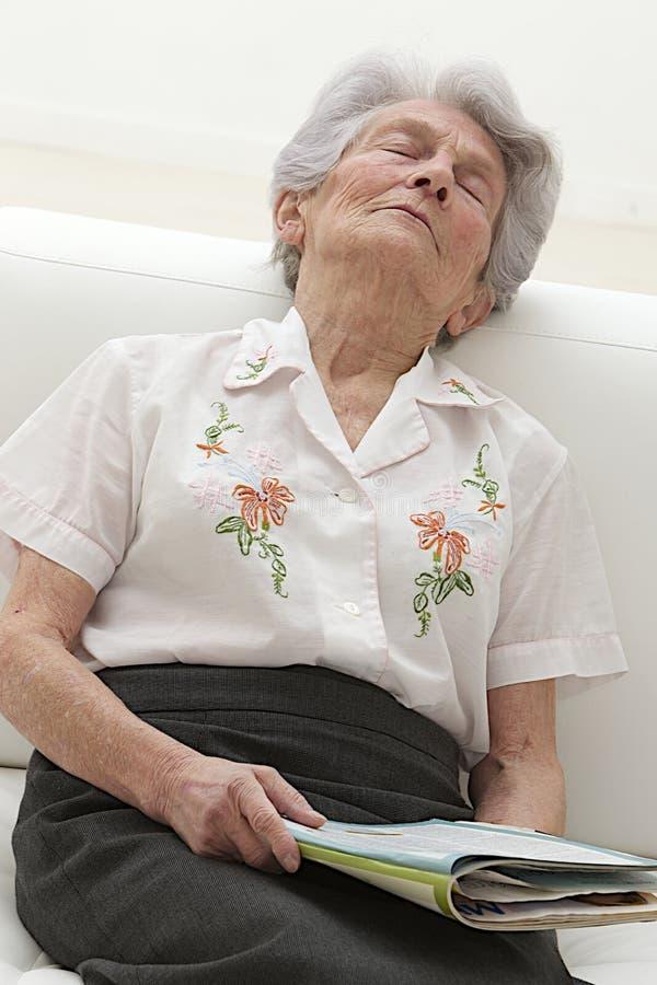 资深妇女睡着在读书 免版税库存图片