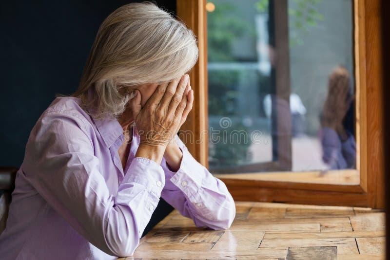 资深妇女覆盖物面孔,当坐在咖啡馆时的桌上 免版税库存图片
