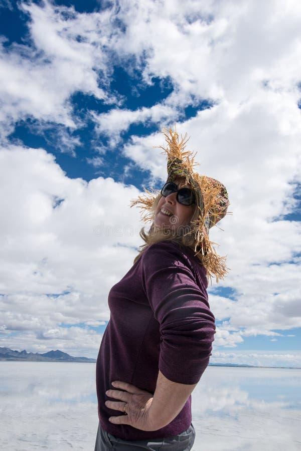 资深妇女触击穿一个愚蠢的草帽的姿势在邦纳维尔盐沼 免版税库存照片