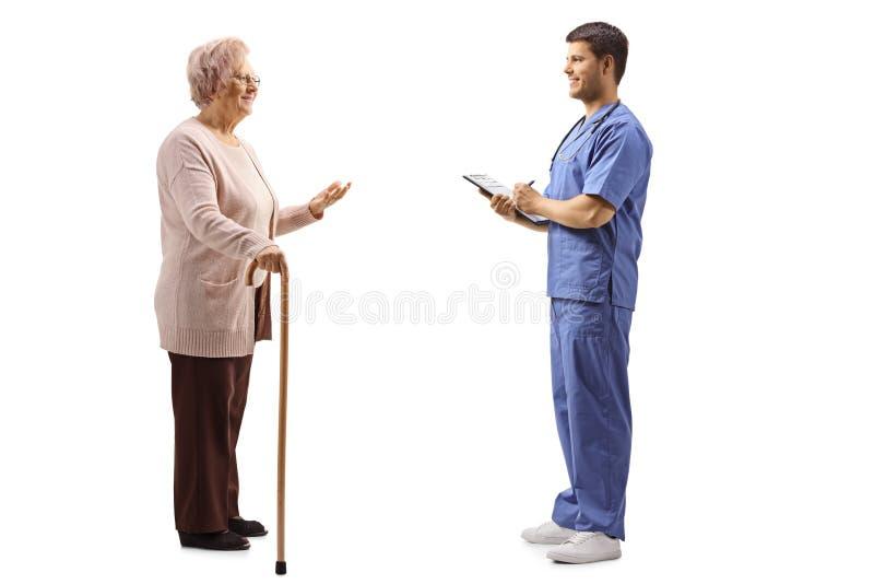 资深妇女谈话与一件蓝色制服的一位年轻男性医生 图库摄影