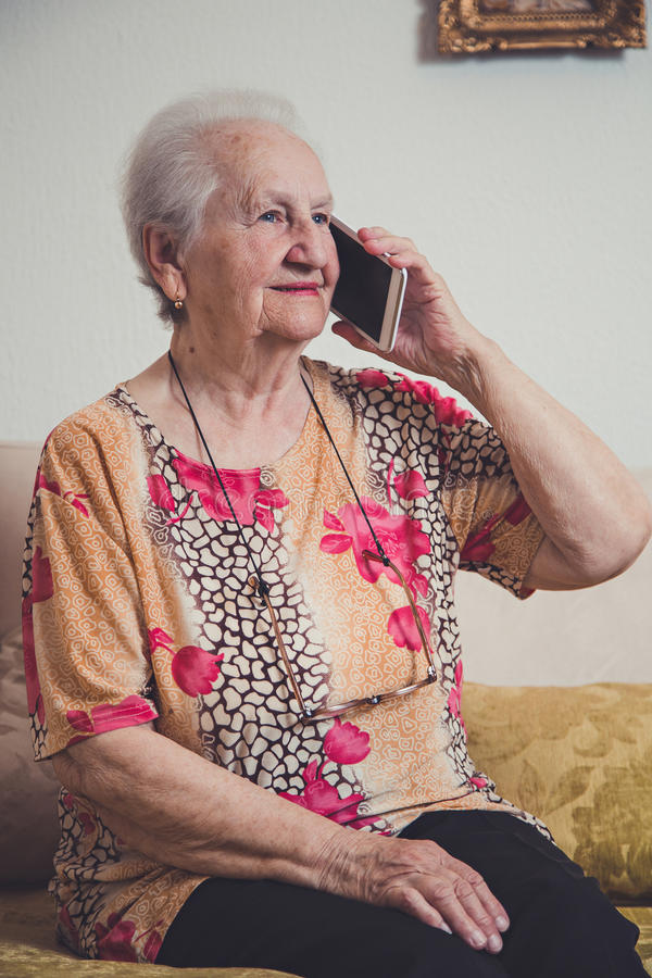 资深妇女谈话在一个手机 库存图片