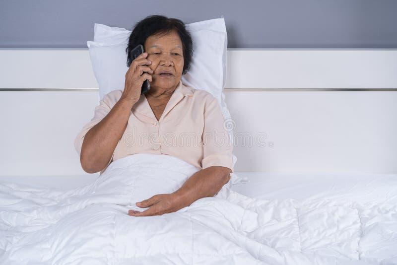 资深妇女谈话在手机在床上 免版税库存图片