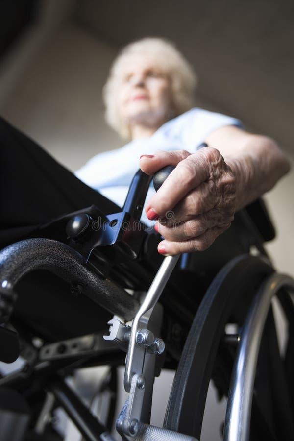 资深妇女运行的轮椅 免版税库存图片