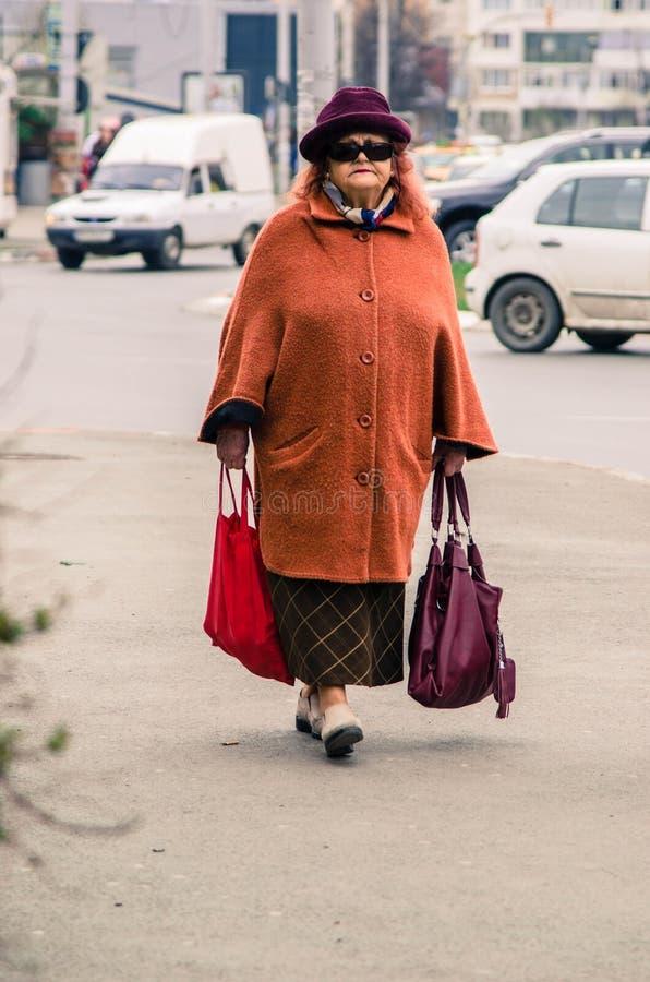 资深妇女运载的购物袋 库存图片