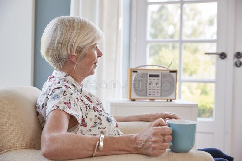 资深妇女饮用的茶和听在家收音 免版税库存照片