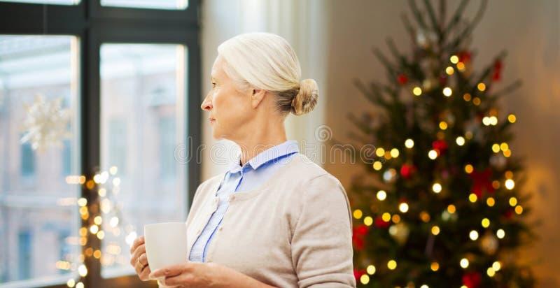 资深妇女饮用的茶或咖啡在圣诞节 库存照片