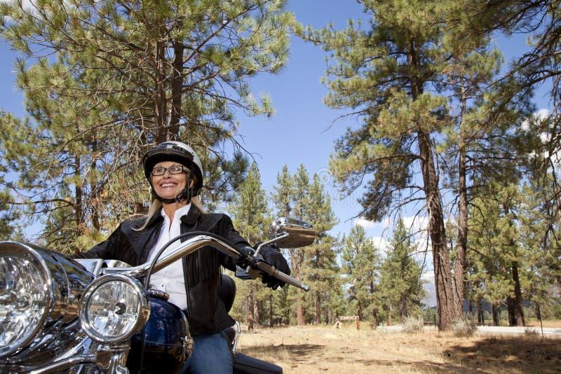资深妇女骑马摩托车通过森林 免版税图库摄影