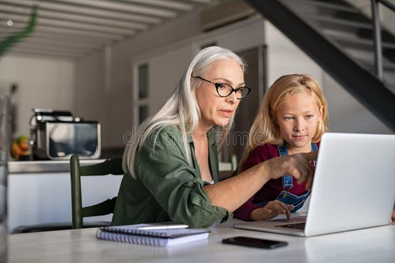 资深学习在膝上型计算机的妇女和孩子 免版税图库摄影