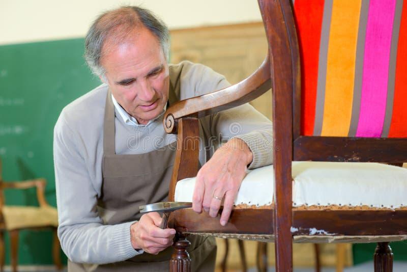 资深家具工修理椅子 免版税图库摄影