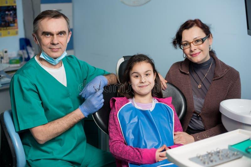 资深小儿科牙医和女孩画象有她的母亲的第一次牙齿参观的在牙齿办公室 免版税库存照片