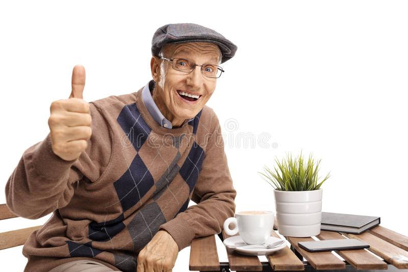资深开会在做赞许姿态的咖啡桌上 免版税库存照片