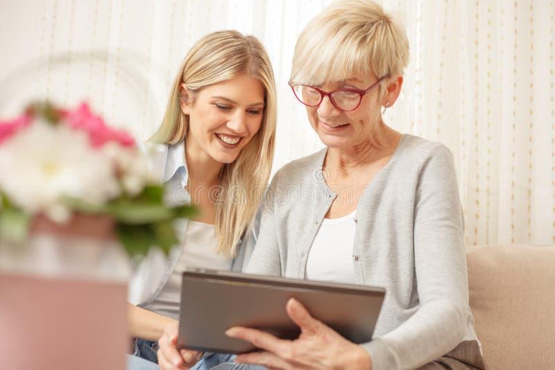 资深微笑和看片剂的母亲和女儿 在前景的花花束 免版税图库摄影