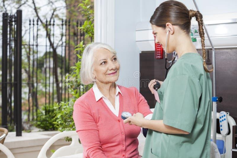 资深患者护士审查的血压  图库摄影