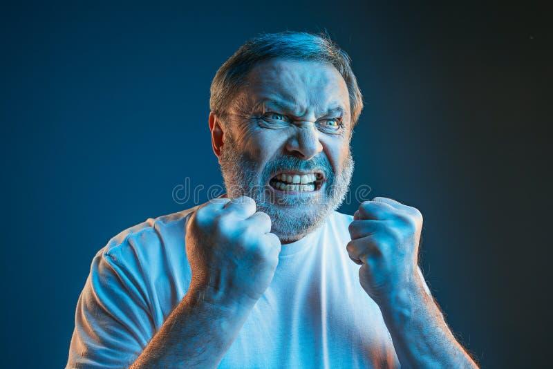 资深情感恼怒的人尖叫在蓝色演播室背景 免版税库存照片