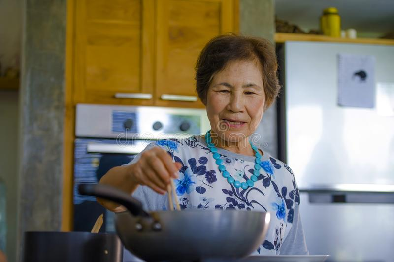 资深愉快和甜亚洲日语生活方式画象退休了在家烹调单独厨房的妇女整洁和整洁 库存图片