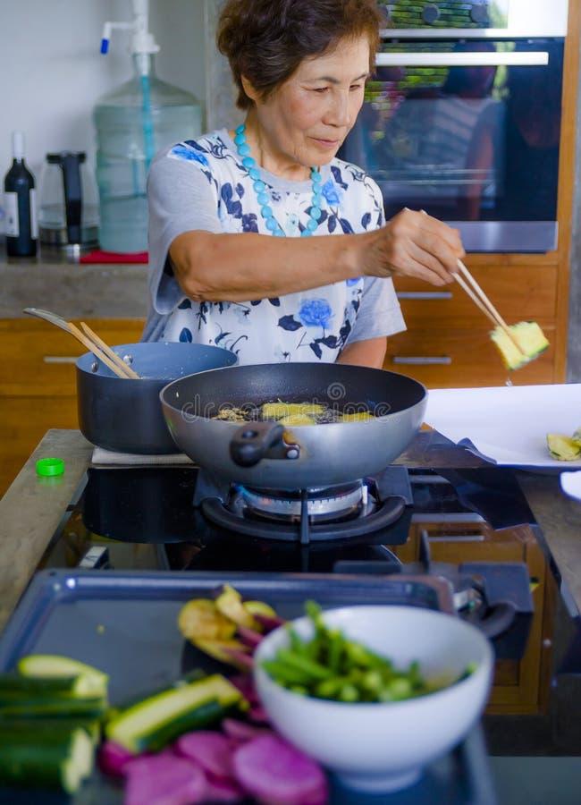 资深愉快和甜亚洲日语生活方式画象退休了在家烹调单独厨房的妇女整洁和整洁 库存照片