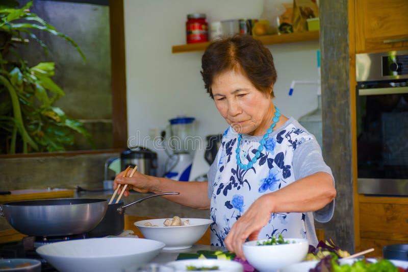 资深愉快和甜亚洲日语生活方式画象退休了在家烹调单独厨房的妇女整洁 免版税库存图片