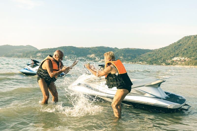 资深愉快的夫妇获得嬉戏的乐趣在普吉岛海滩的jetski 免版税库存照片