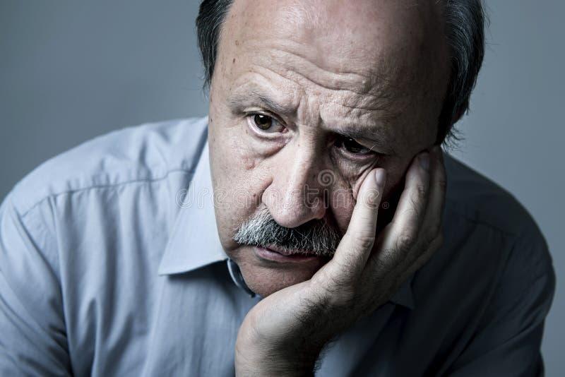资深成熟老人顶头画象看起来他的70s的哀伤和担心的遭受的老年痴呆症 库存照片