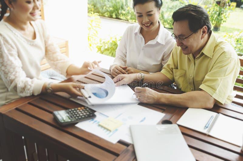 资深投资的夫妇会议财政顾问,更老的客户准备买医疗健康生命保险咨询的经纪 库存图片