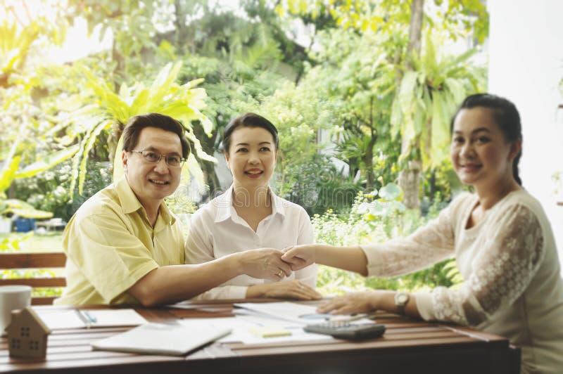 资深投资的夫妇会议财政顾问,更老的客户准备买医疗健康生命保险咨询的经纪 免版税库存图片