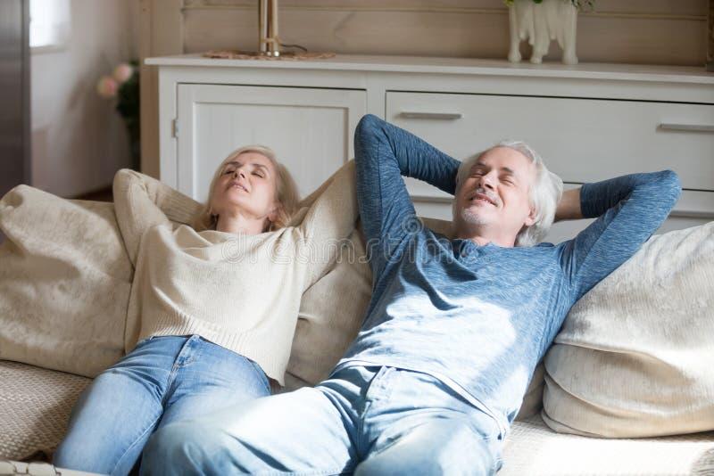 资深放松在有眼睛的长沙发的丈夫和妻子关闭了 库存照片