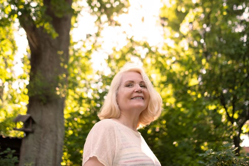 资深斯堪的纳维亚妇女在树微笑之间的夏天庭院里 库存图片