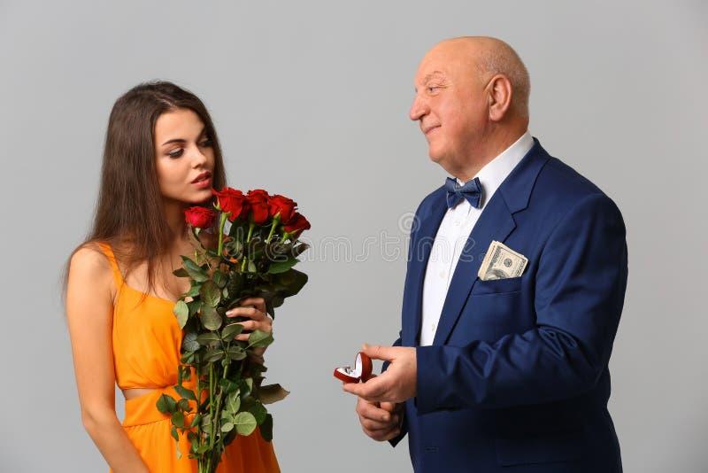 资深有钱人提议对灰色背景的年轻女人 权宜婚姻 库存照片