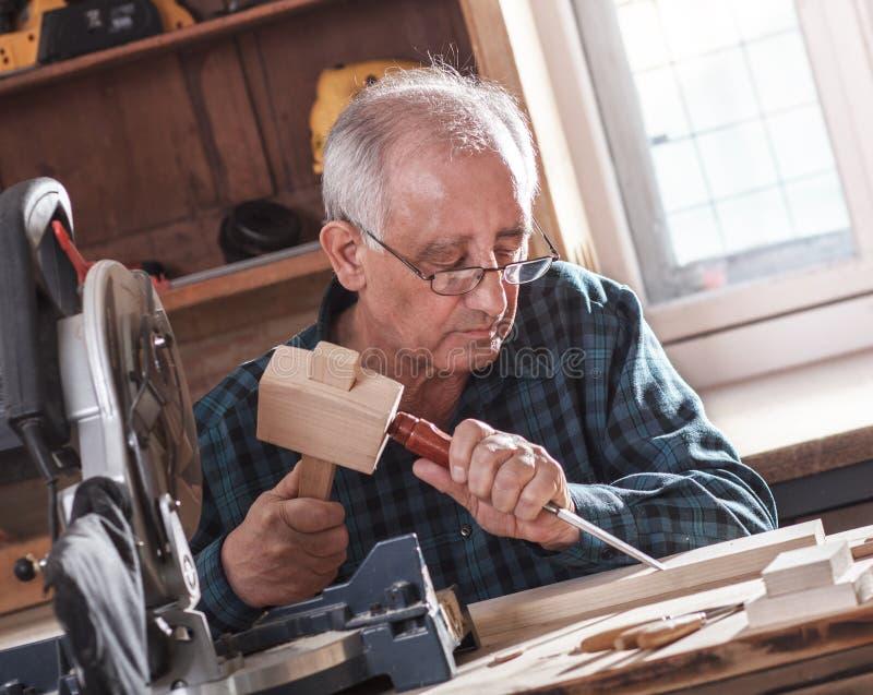 资深木匠与工具一起使用 免版税图库摄影