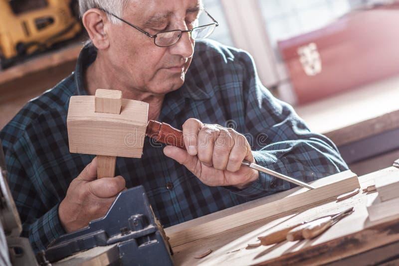 资深木匠与工具一起使用 免版税库存照片