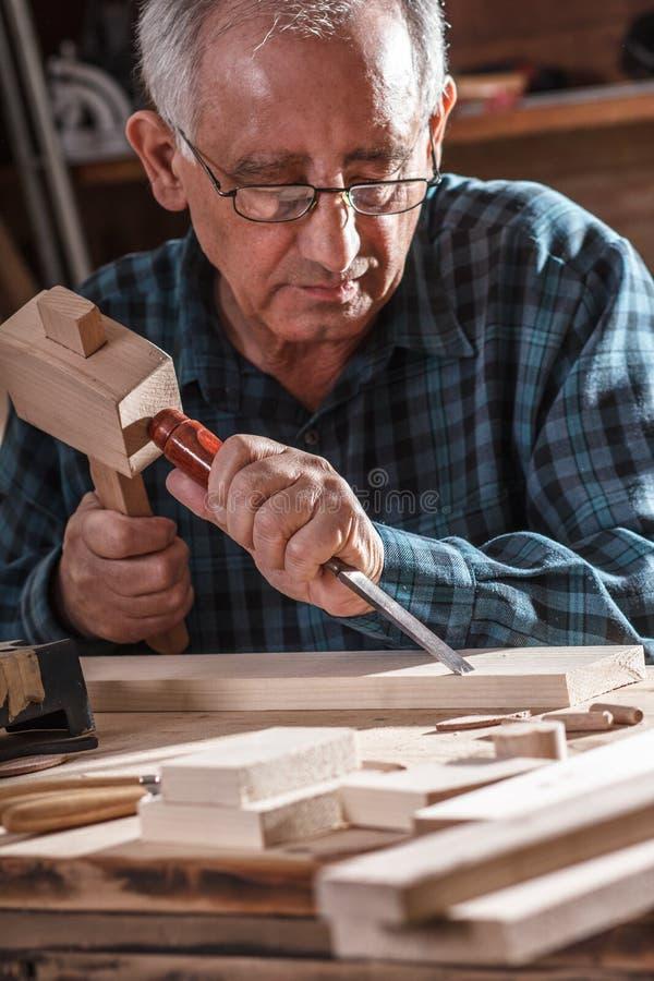 资深木匠与工具一起使用 免版税库存图片