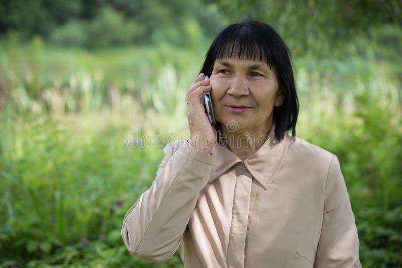 资深楚瓦什人妇女讲话由在夏天绿色背景的电话 免版税库存图片