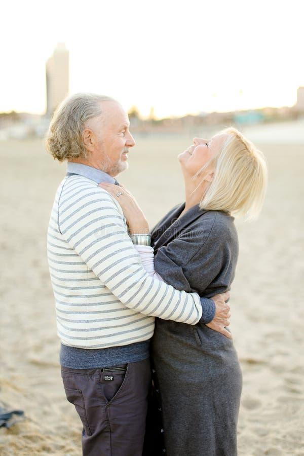 资深欧洲丈夫在沙滩背景中的拥抱妻子 库存照片