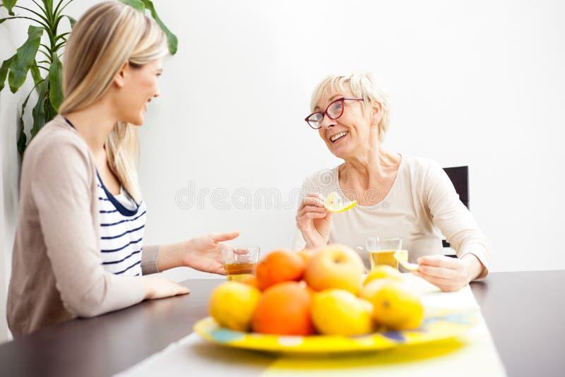 资深母亲和女儿谈的和饮用的茶在明亮地被点燃的餐厅 免版税库存图片