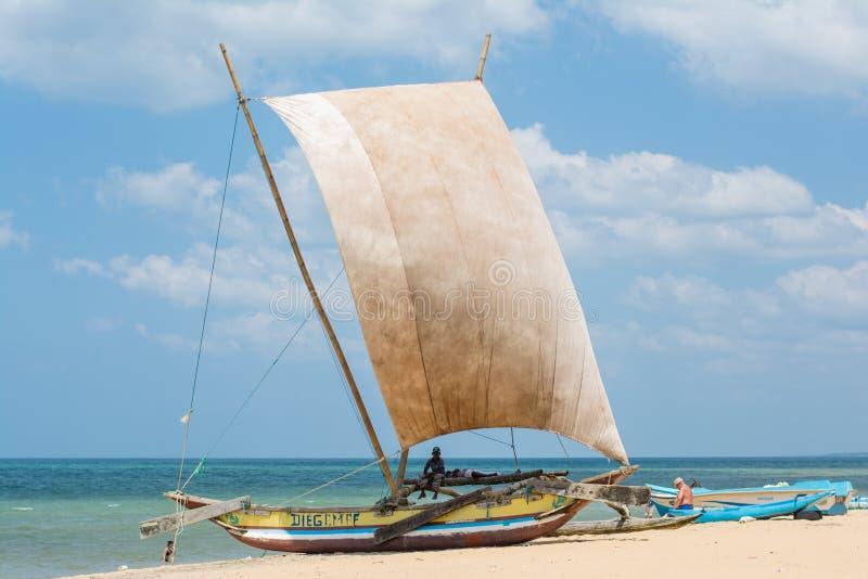 资深水手坐在海滩的帆船 免版税库存照片