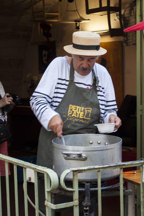 资深法国人烹调一个传统法国盘在Mirandela dels艺术节期间在Pézenas,法国南部 免版税库存照片