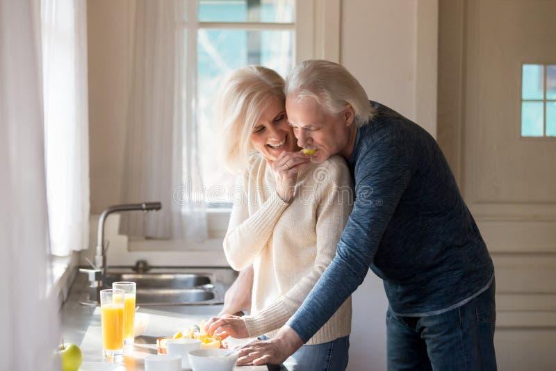 资深爱恋的夫妇获得在家烹调早餐的乐趣 库存图片