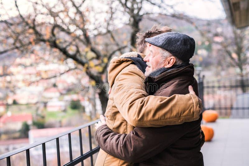 资深父亲和他的年轻儿子步行的 免版税库存照片